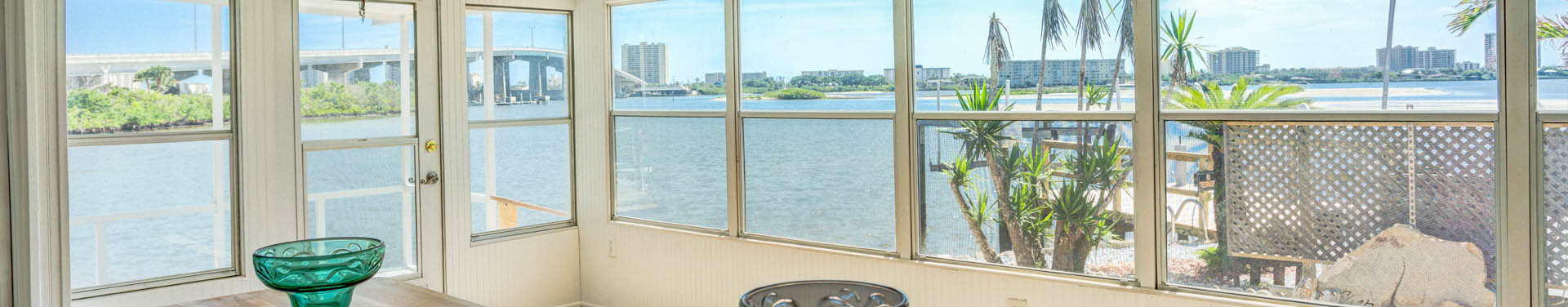 Photo of the view of the blue ocean and bridge over the water from inside a manufactured home through glass windows