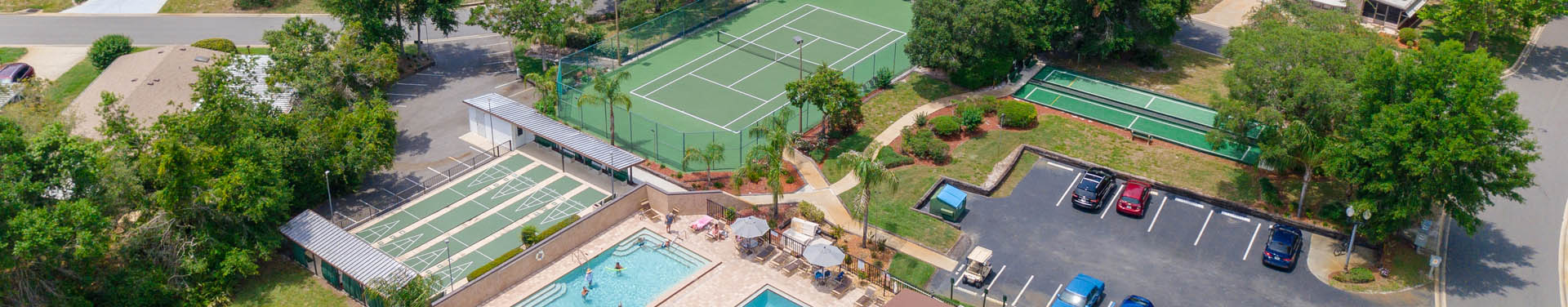 Photo of tennis court, pools, parking lot, shuffle board courts, and trees taken from a drone in the sky looking down