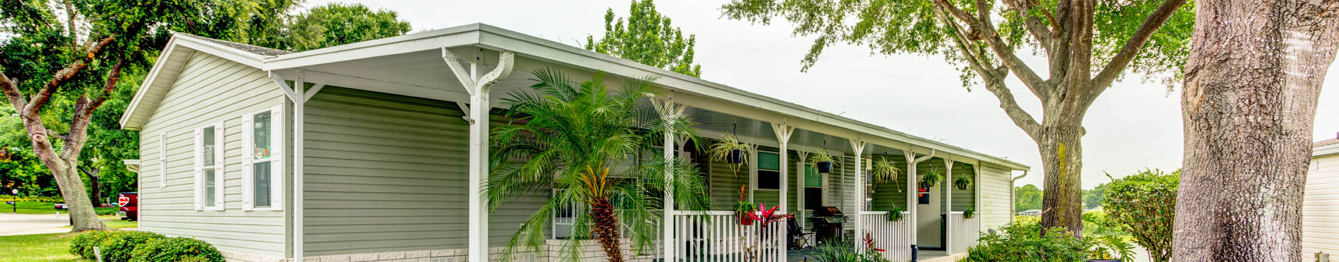 Photo of a mobile home with a nice front porch and greenish siding, surrounded by trees