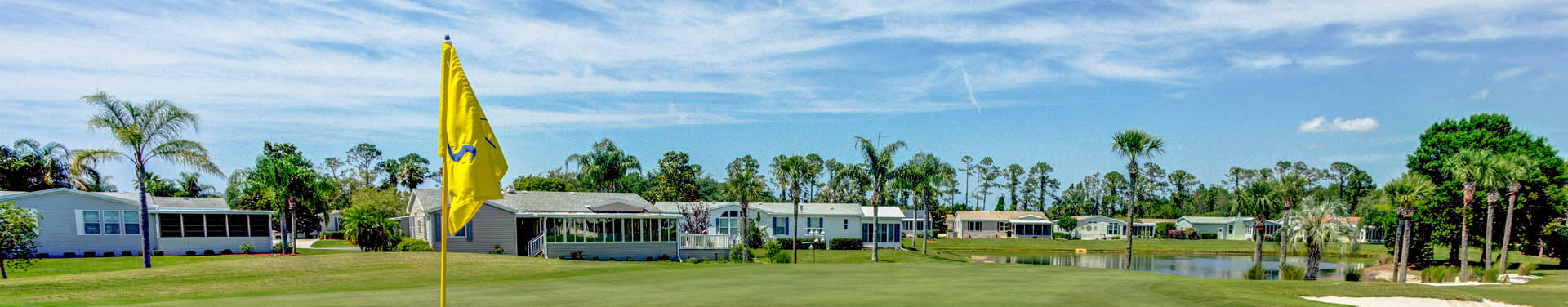 Photo of the lush green golf field surrounded by the community of mobile homes, with nice green trees